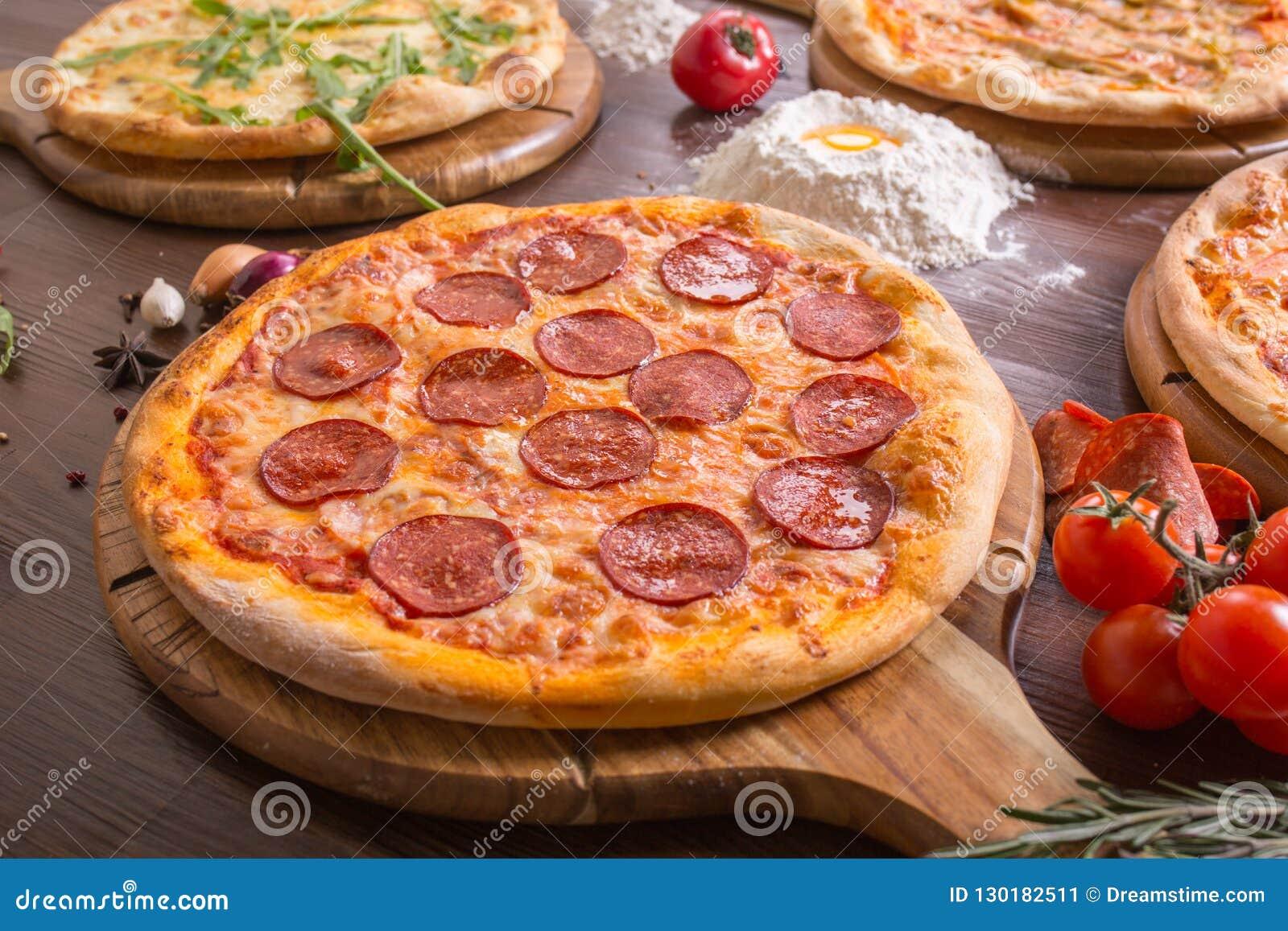 Pizza classificada com pepperoni, carne, margarita em um suporte de madeira