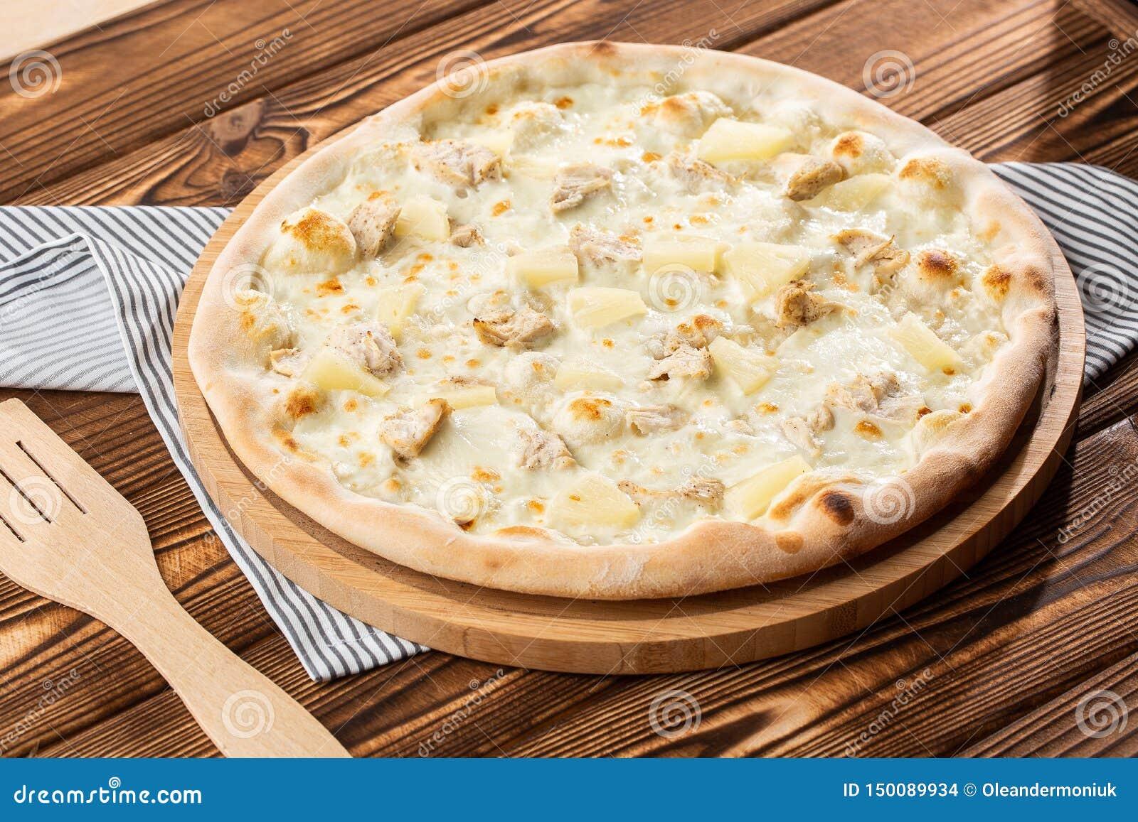 A pizza cobriu com saque do molho, da galinha, do queijo e do abacaxi na placa de madeira na tabela de madeira Foto da pizza hava