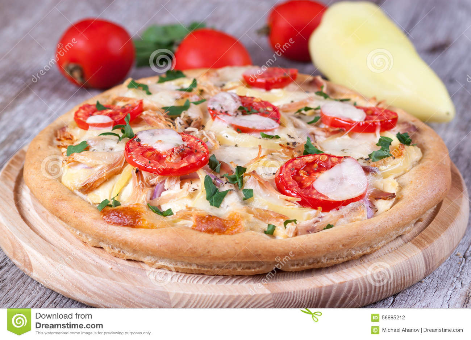 Pizza con il pollo, i pomodori ed il formaggio su un bordo di legno