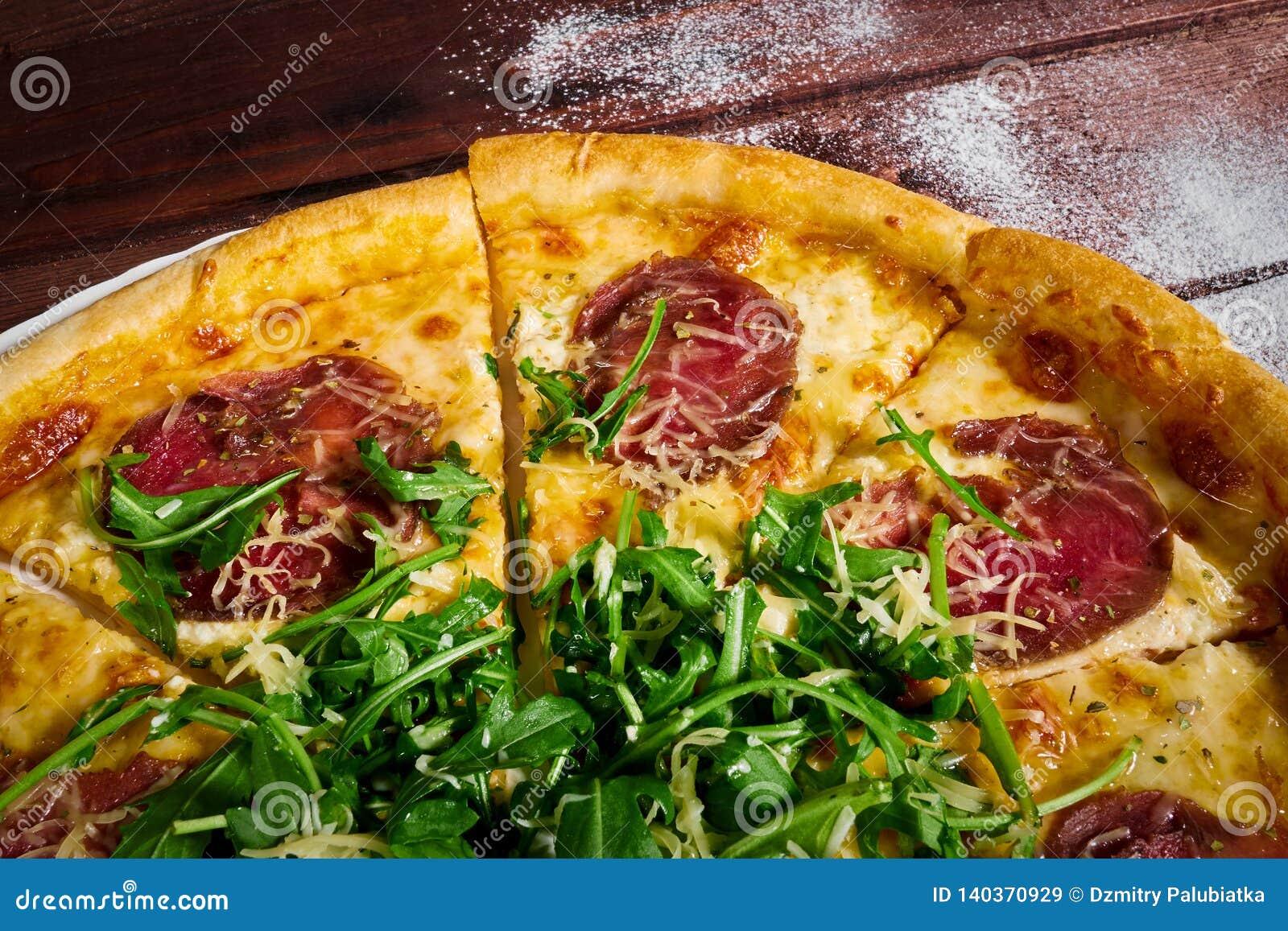 Pizza cortada com carne e fim-u dos verdes