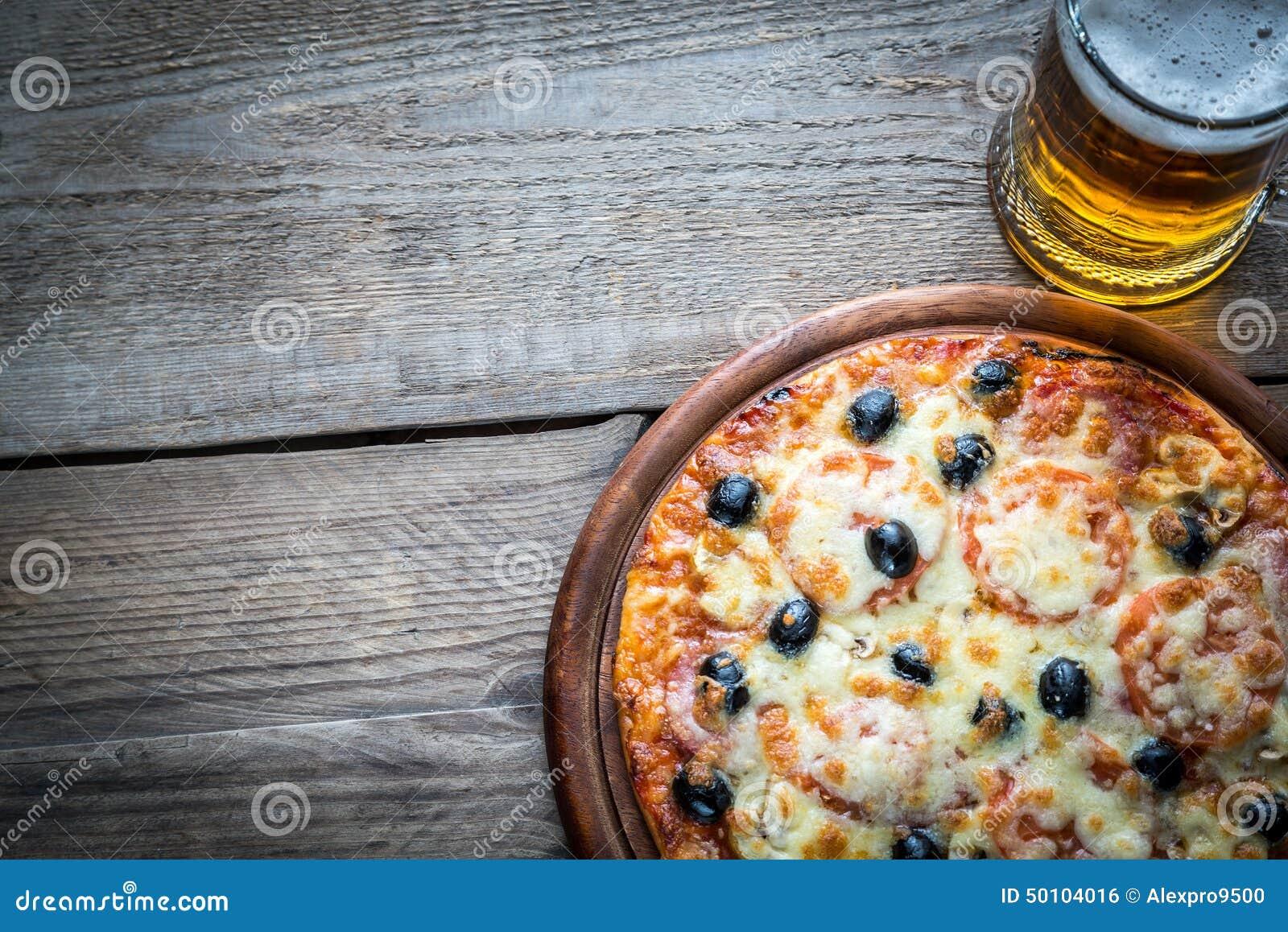 Pizza cozinhada com um vidro da cerveja