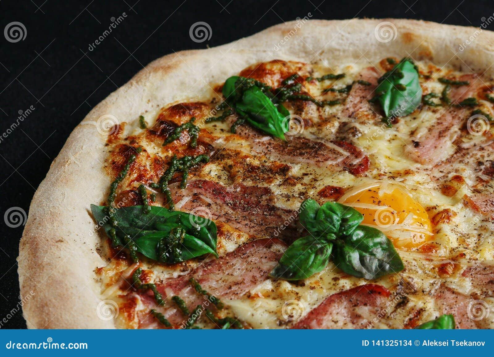 Pizza de Carbonara con cierre de tocino y del huevo para arriba en fondo oscuro