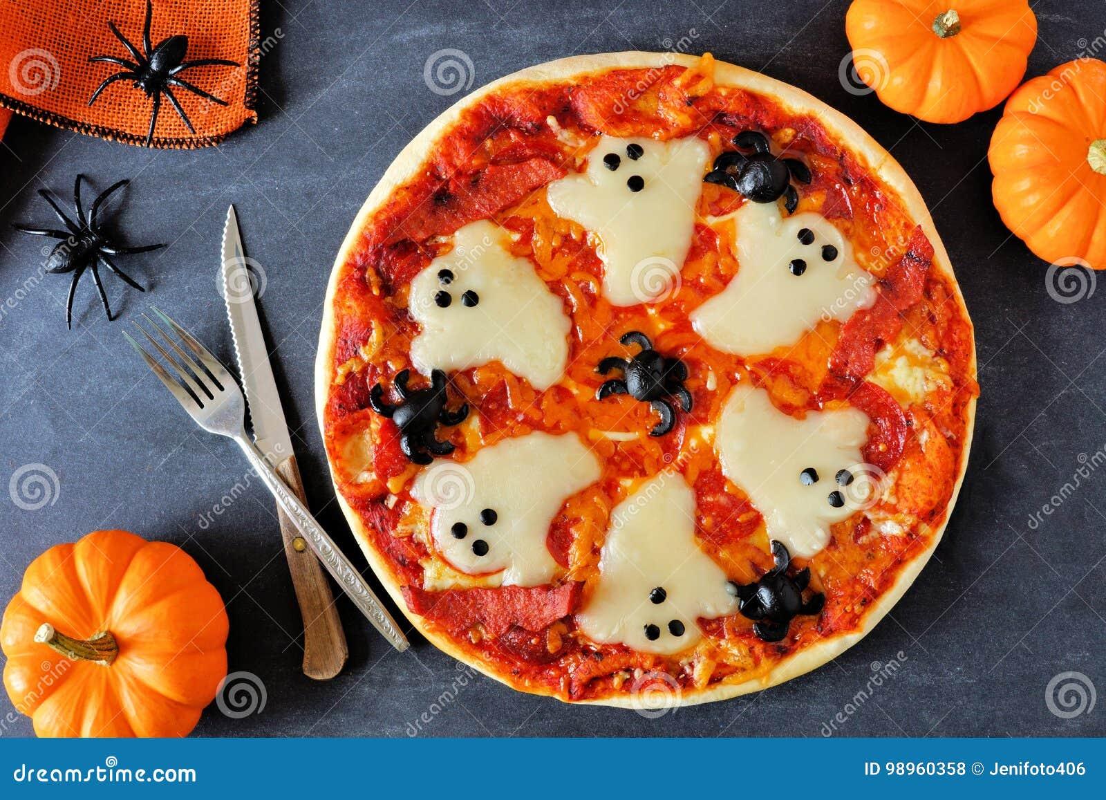 Pizza de Halloween, sobre escena con la decoración en fondo negro