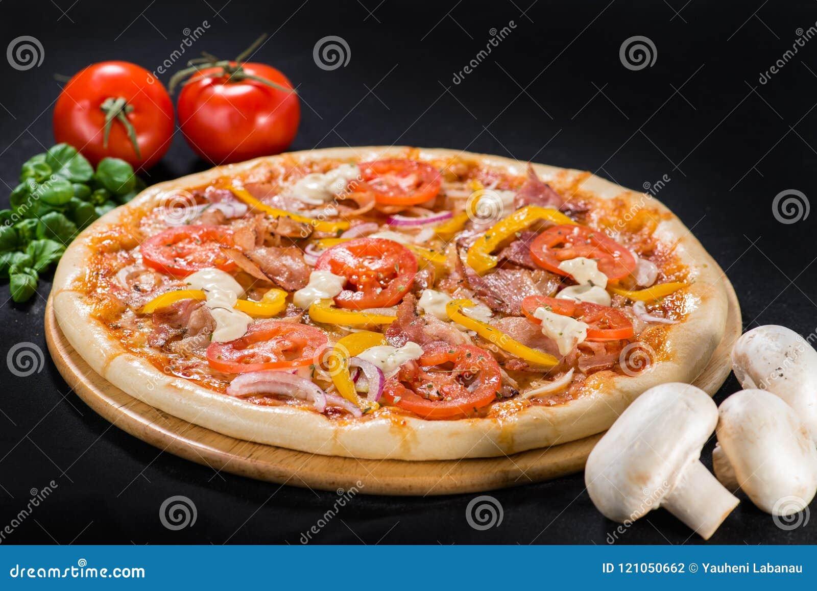 Pizza de luxe avec du mozzarella, salami, lard, oignon, tomates