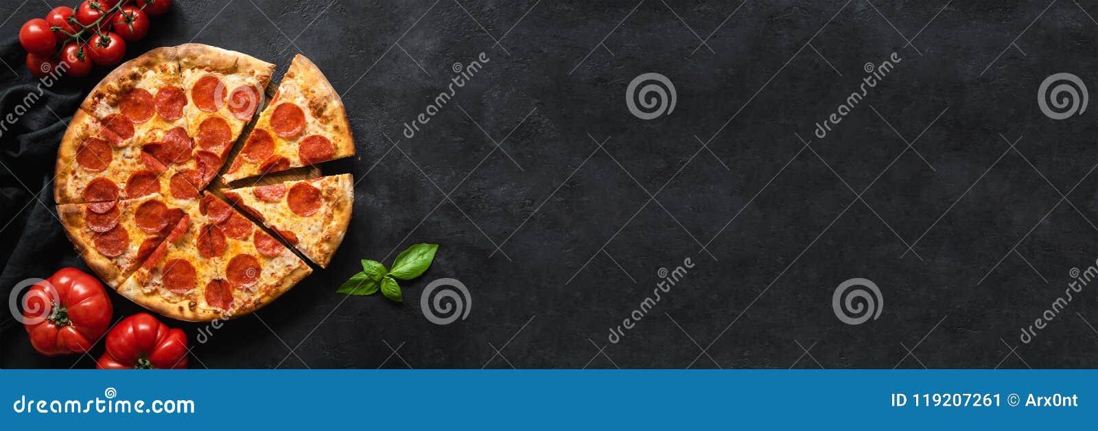 Pizza de salchichones sabrosa y cocinar los tomates de los ingredientes, especias, albahaca en fondo concreto negro