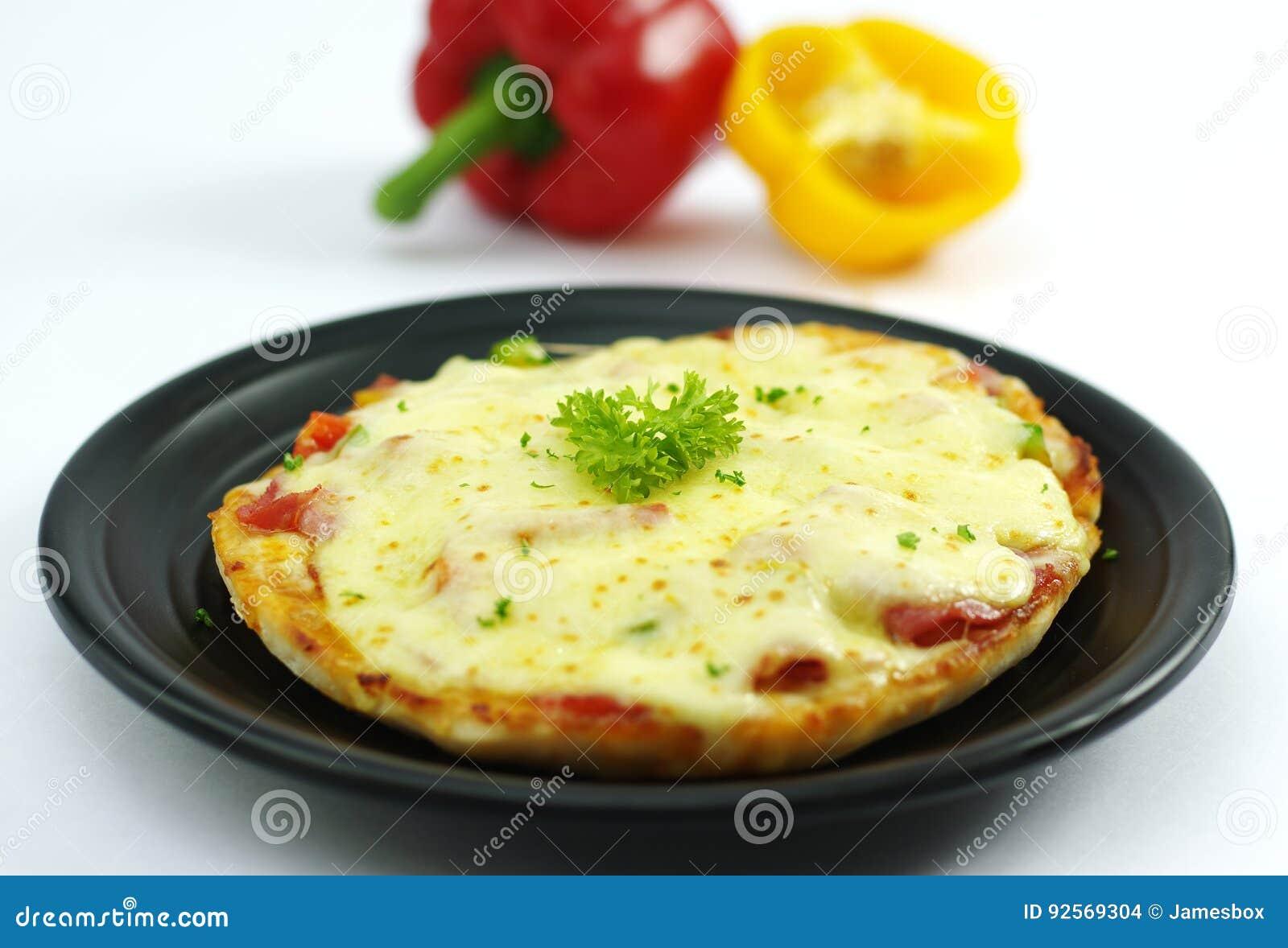 Pizza del pollo nello stile coreano con peperone dolce sul piatto nero