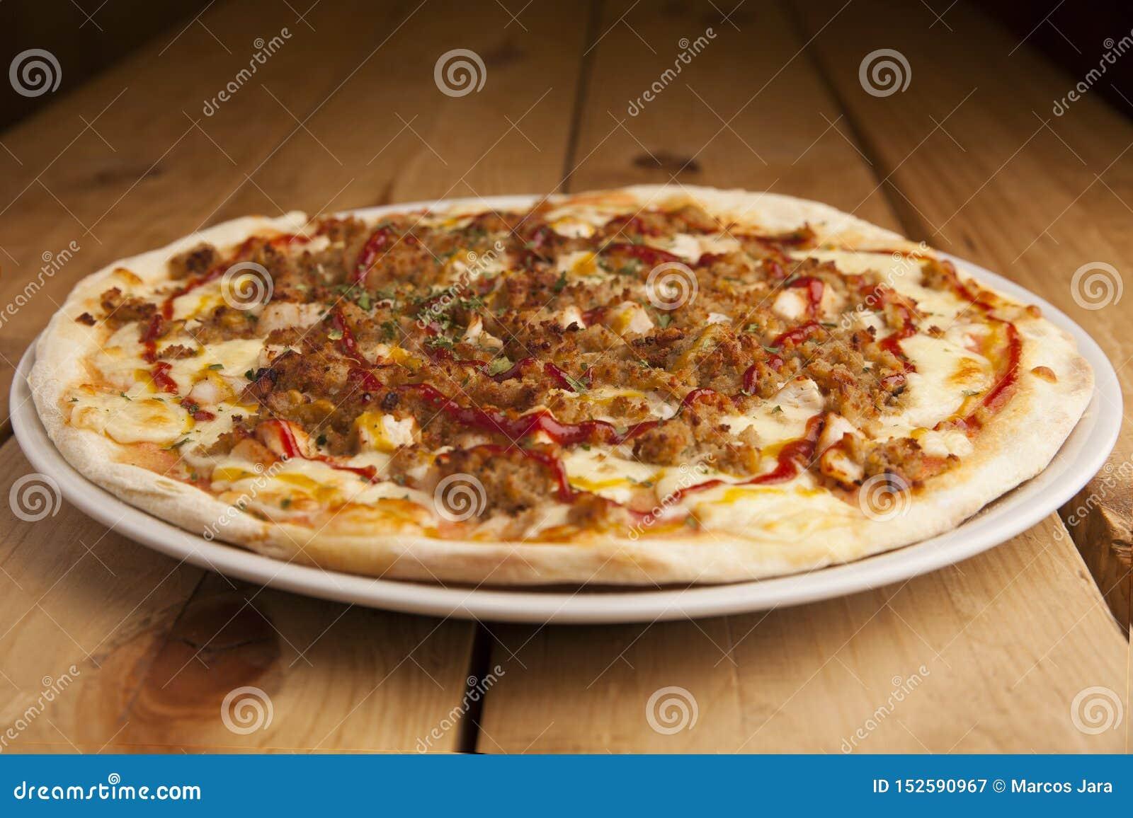 Pizza deliciosa de la barbacoa en una tabla de madera