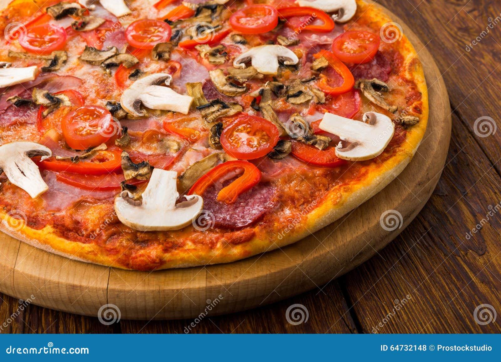 Pizza deliziosa con i funghi, i peperoni e le merguez