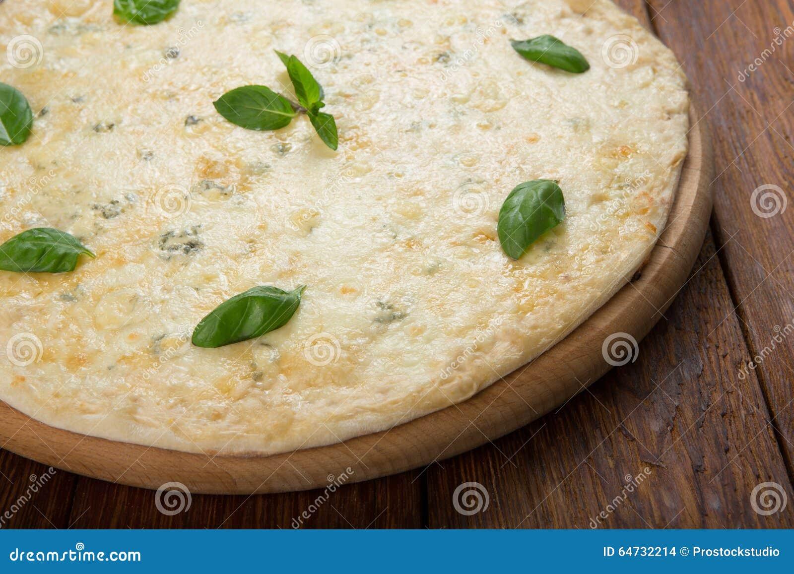 Pizza di formaggio deliziosa quattro con le foglie del basilico