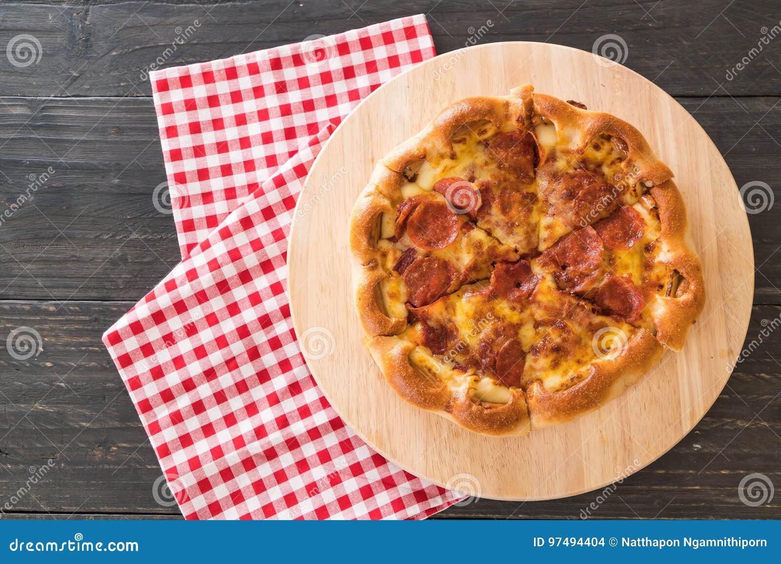 Pizza di merguez casalinga sul piatto di legno