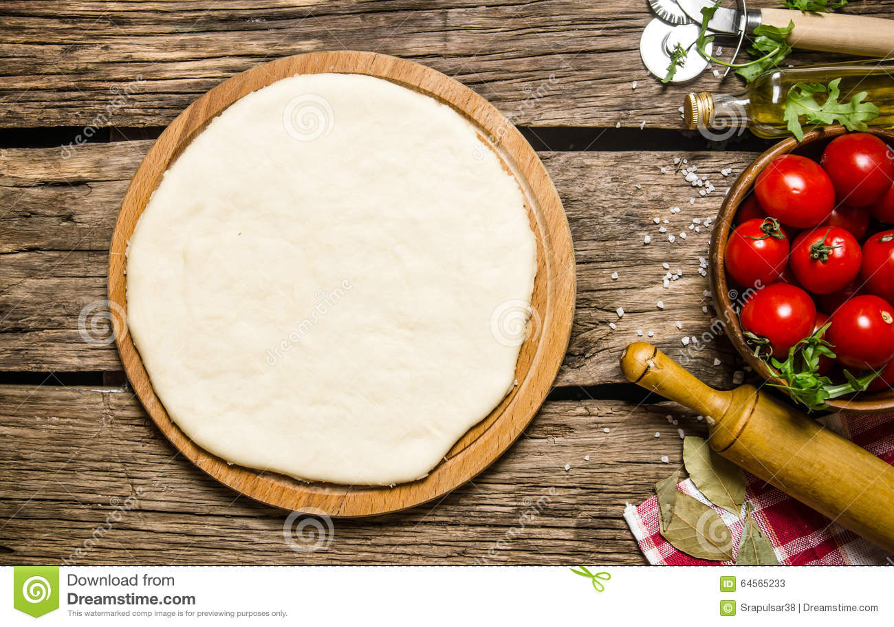 Pizza dough with tomatoes, and herbs with a rolling pin.