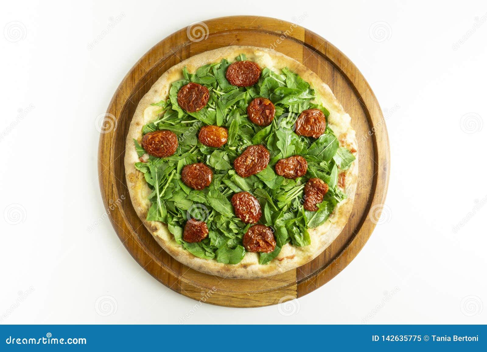 Pizza grande com rucula e tomate seco no fundo branco