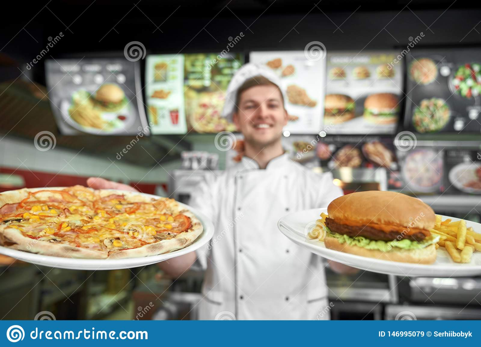 Pizza and haumburger with free potato in hands of male cook