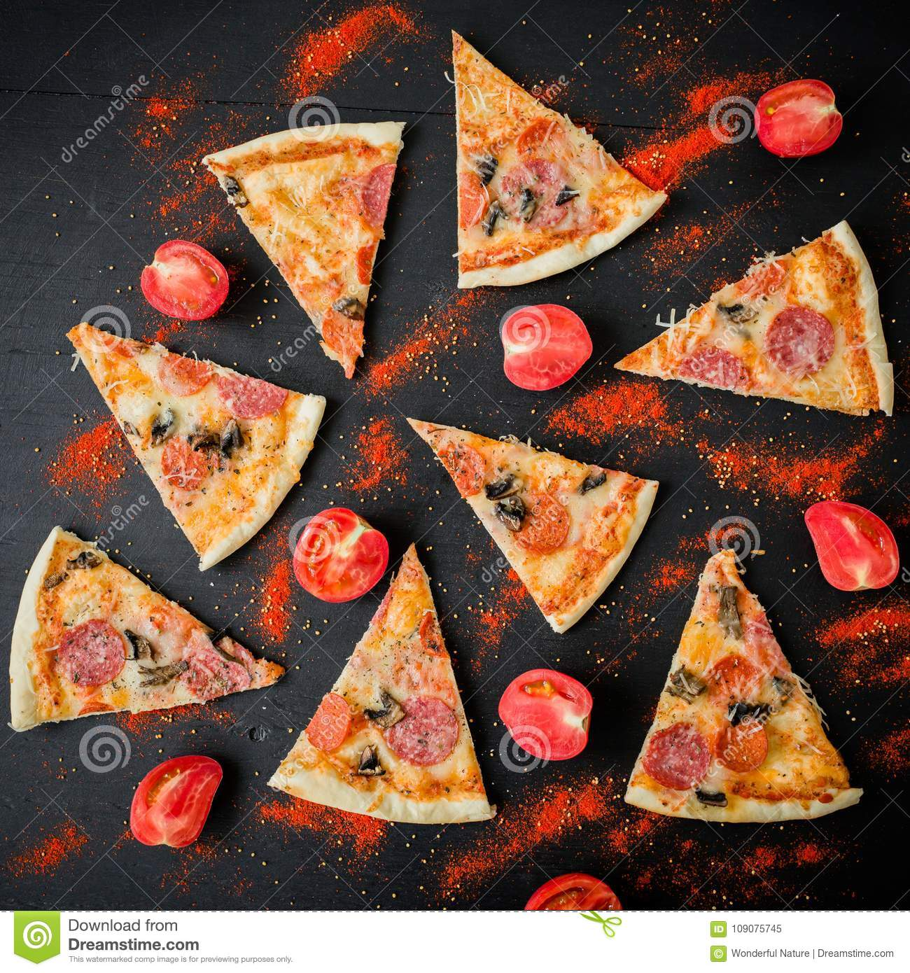 Pizza with ingredients on dark table. Pattern of pizza slices and tomato. Flat lay, top view.