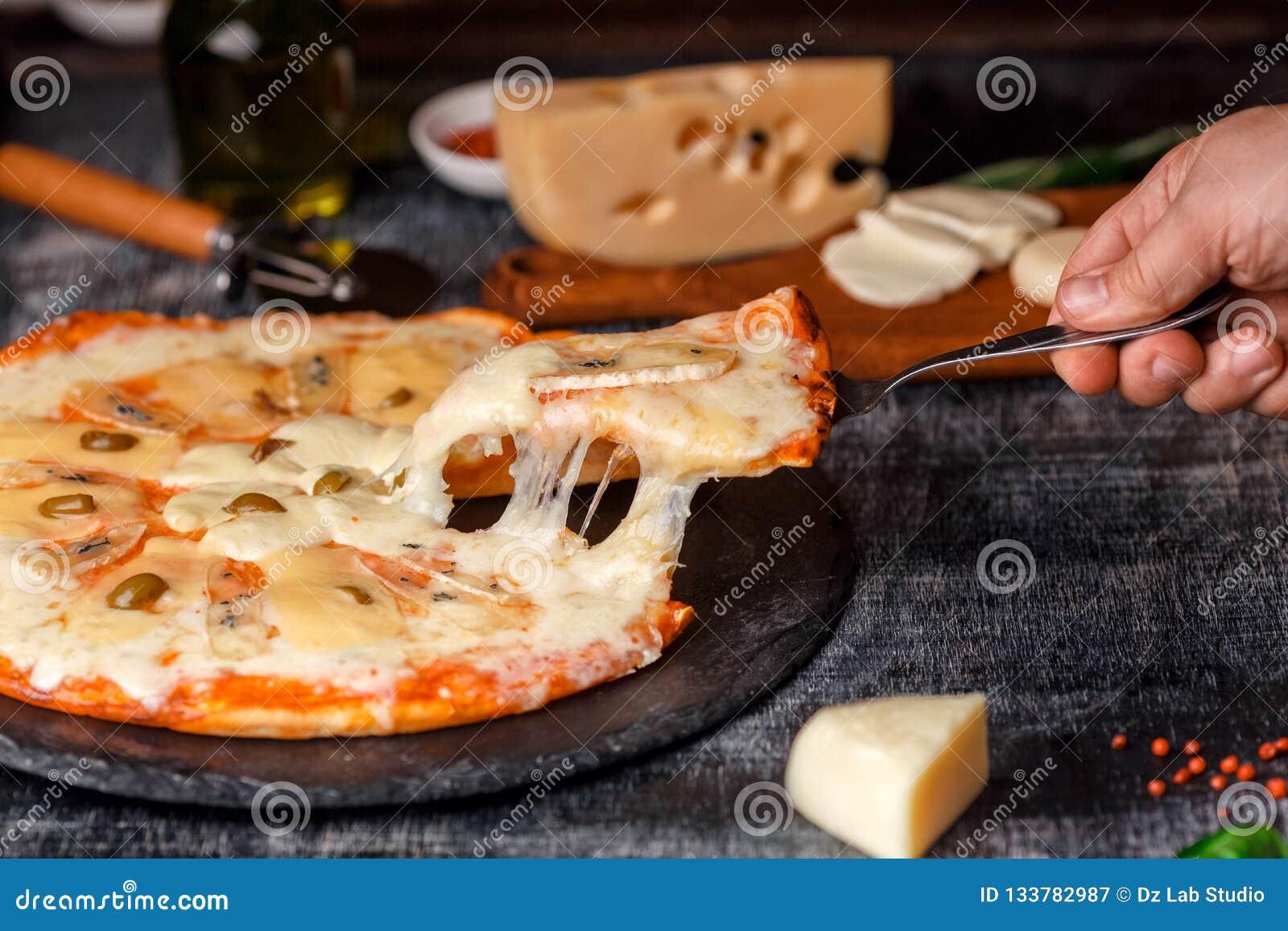 Pizza italienne avec différentes sortes de fromage sur une pierre et un panneau de craie rayé noir Nourriture traditionnelle ital