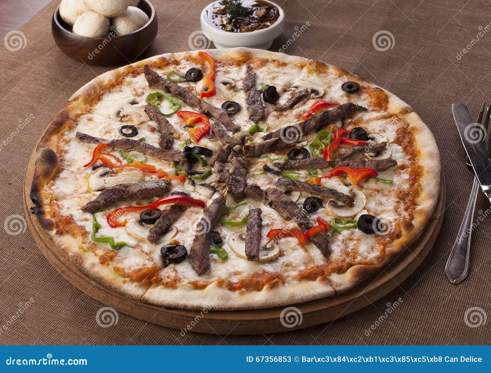 Pizza med nötköttstycken och champinjonen på en brun bakgrund
