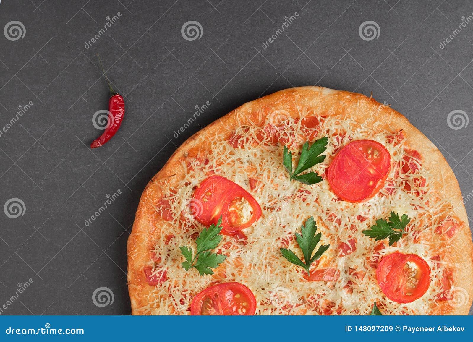 Pizza med tomaten och röd chili på den gråa tabellen, bästa sikt och stället för text