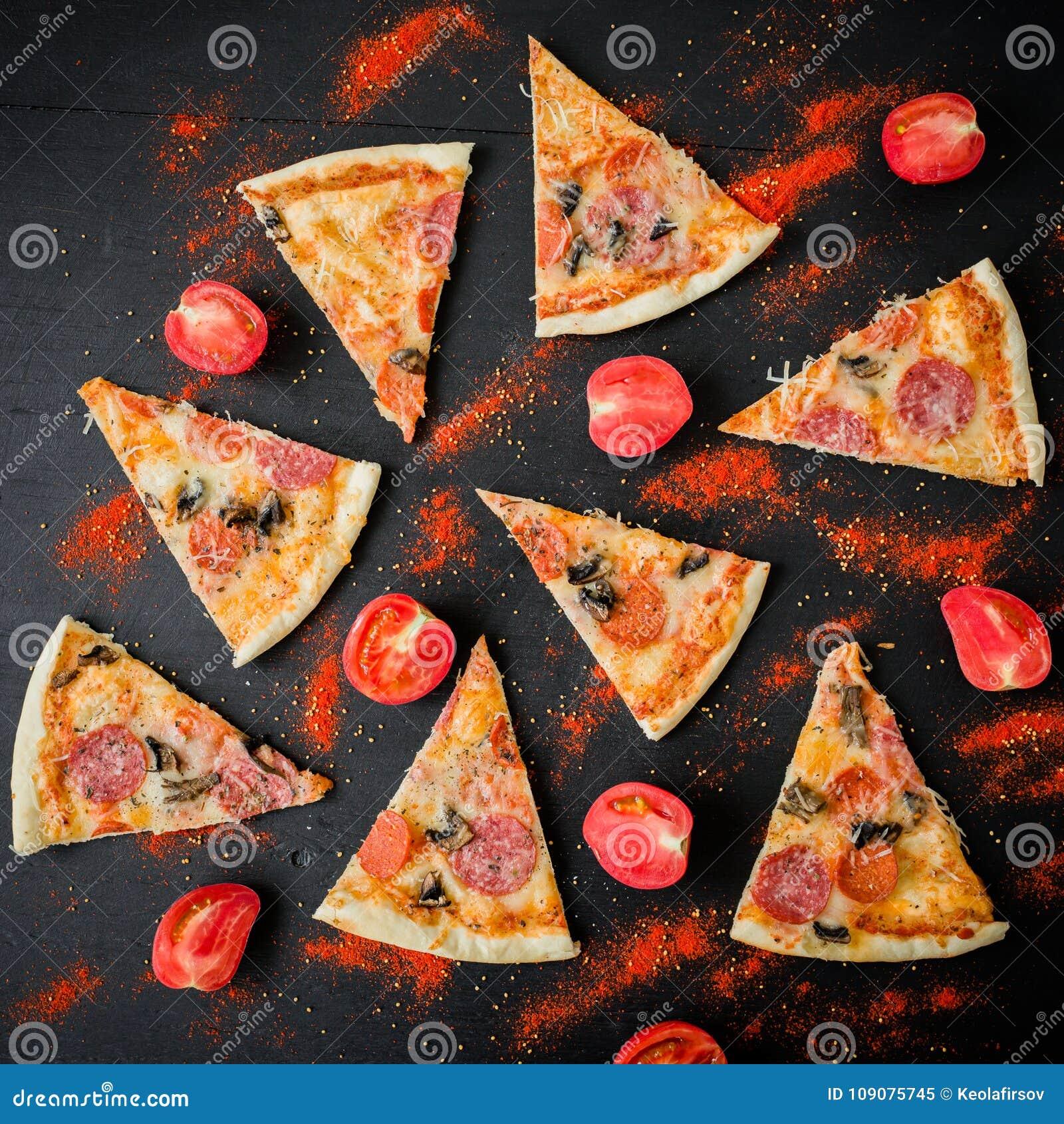 Pizza met ingrediënten op donkere lijst Patroon van pizzaplakken en tomaat Vlak leg, hoogste mening