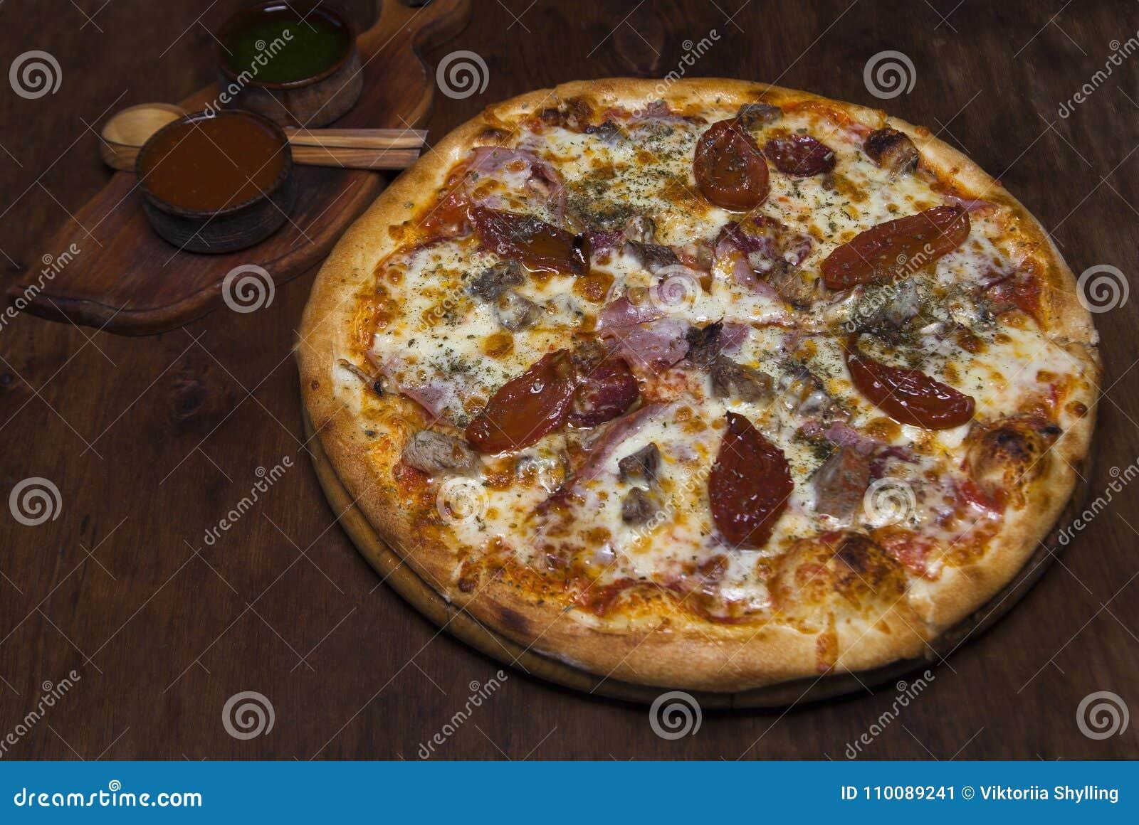 Pizza met kalfsvlees, ham, kaas en in de zon gedroogde tomaten