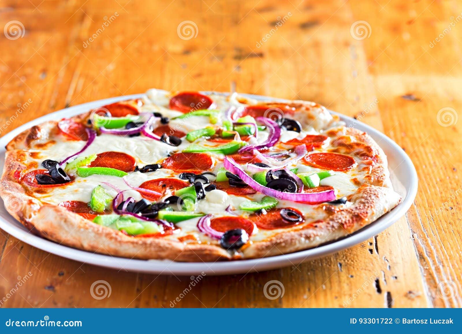 Pizza mit Salami, roter Zwiebel, Pfeffern und schwarzen Oliven