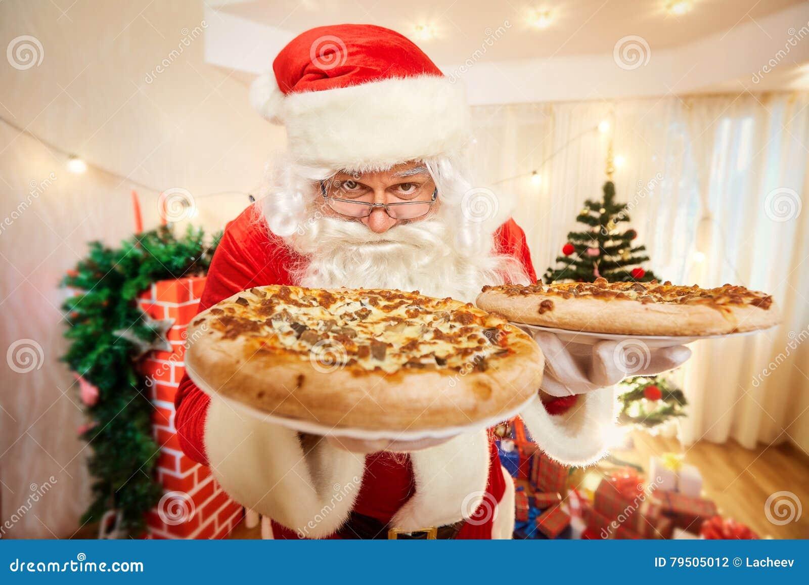 Pizza nas mãos de Santa Claus no Natal, ano novo feliz c