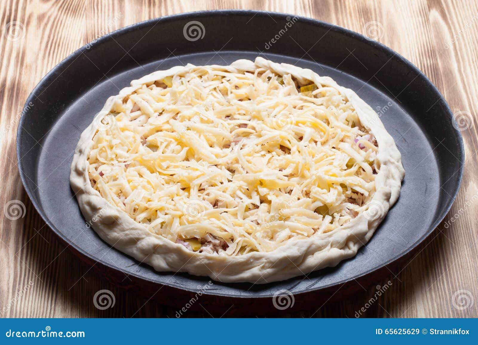 Pizza non préparée avec du fromage râpé