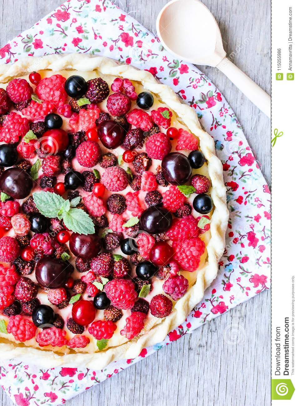 Pizza pie with mascarpone cream cheese, raspberry, black currant, strawberry, cherry on a wooden table. Homemade pie. Fruit pizza.