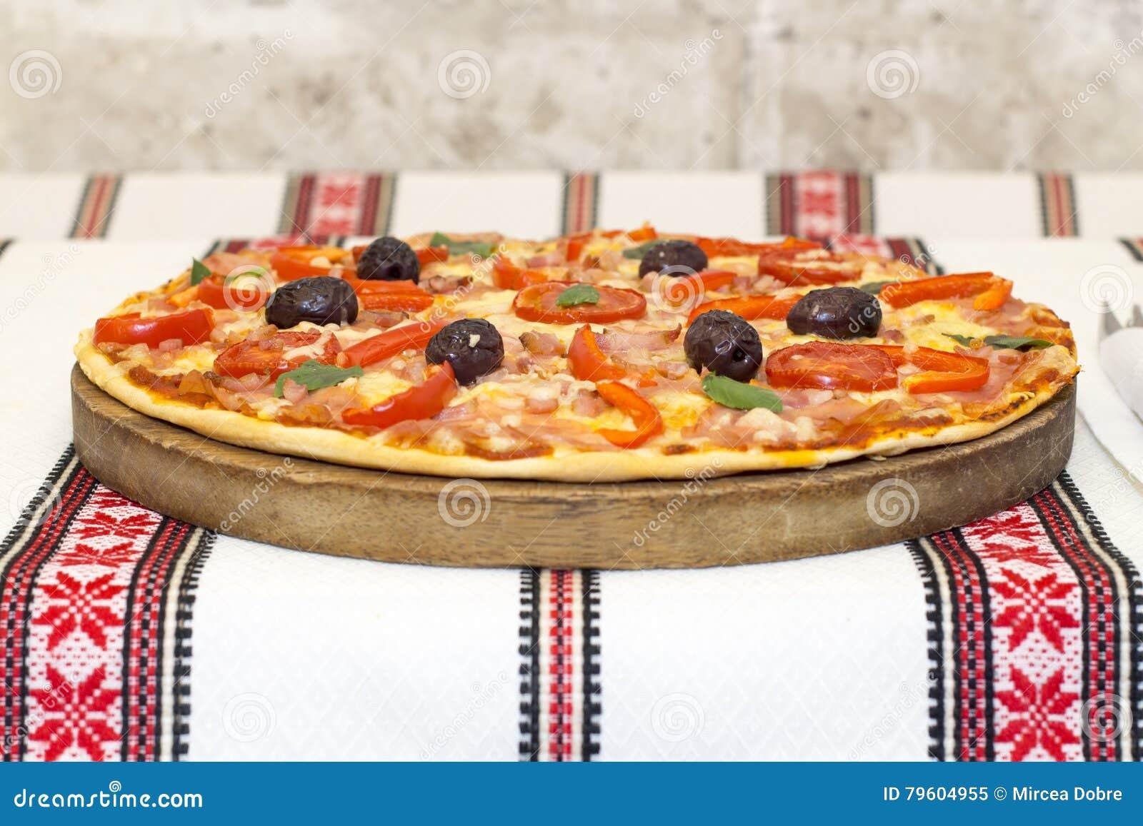 Pizza saboroso com vegetais, manjericão, azeitonas, tomates, pimenta verde na placa de corte, colorido tradicional de pano de tab