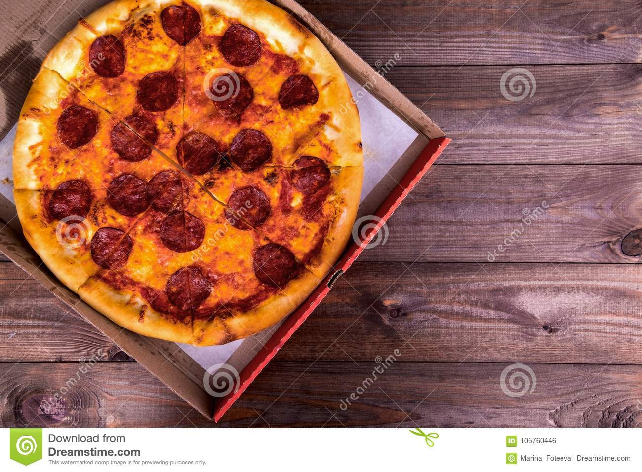 Pizza With Salami In A Box On A Wooden Background With Copy