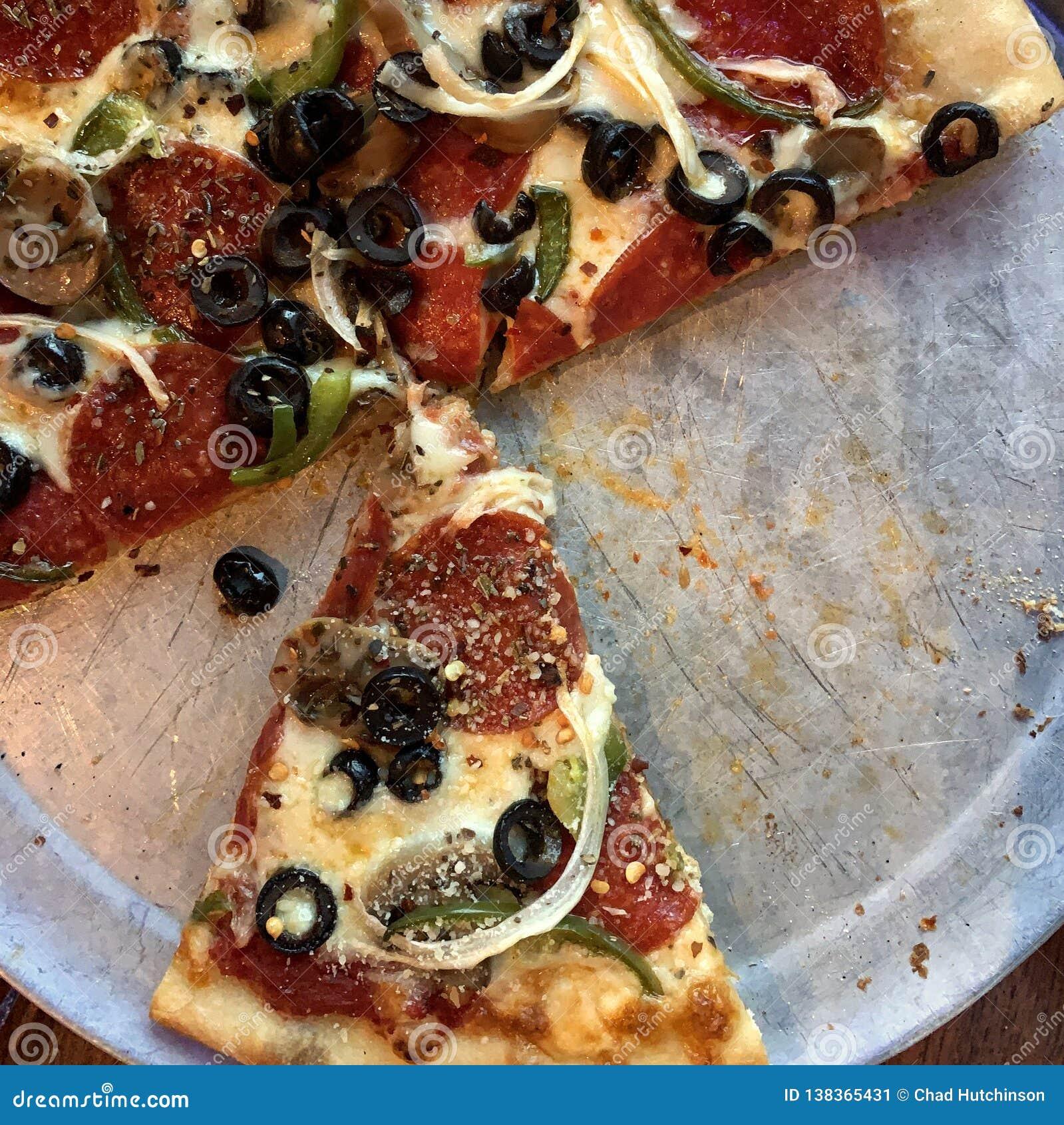 Pizza suprema en una cacerola de aluminio con la falta de las rebanadas