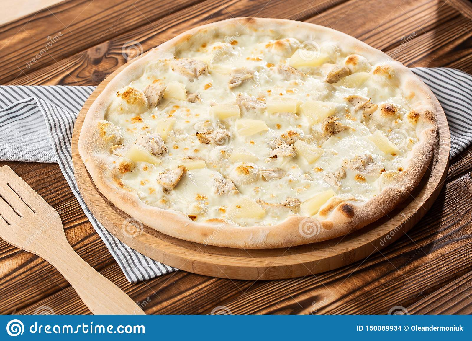 Pizza topped with sauce, chicken, cheese and pineapple serve on wooden plate on wooden table. Photo of Hawaiian pizza.
