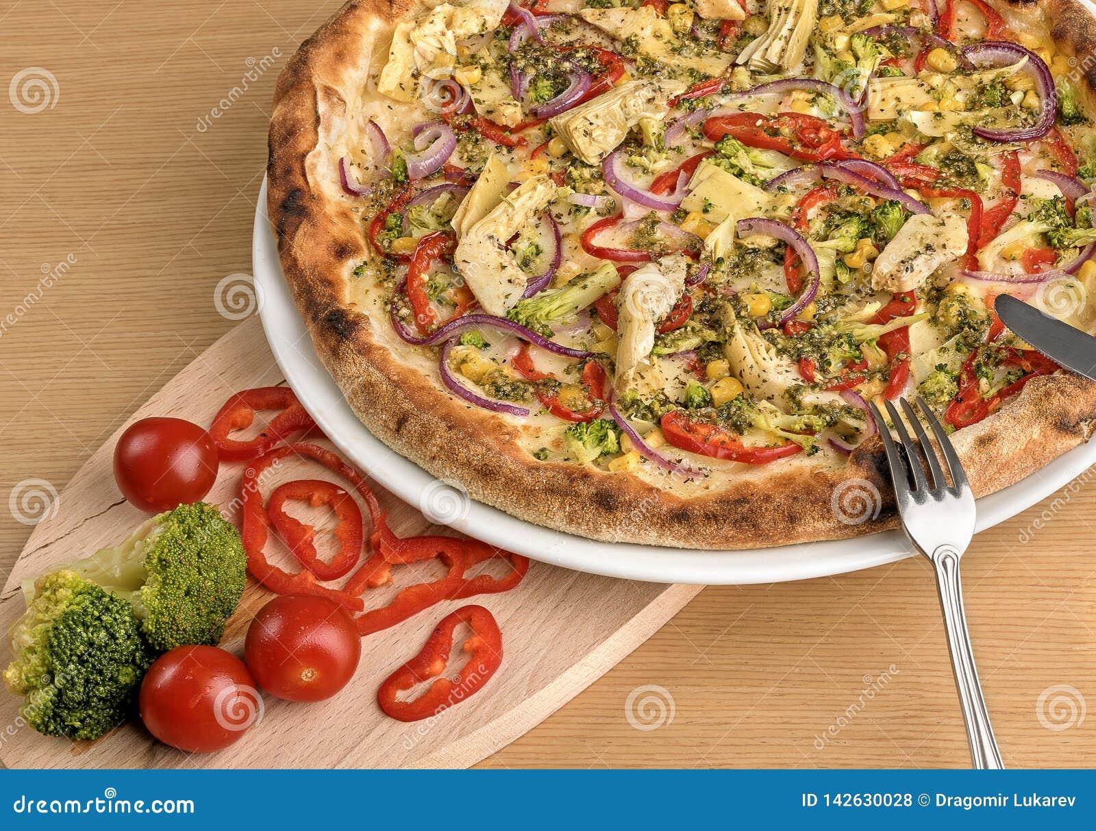 Pizza vegetariana italiana fresca con i broccoli ed i pomodori ciliegia