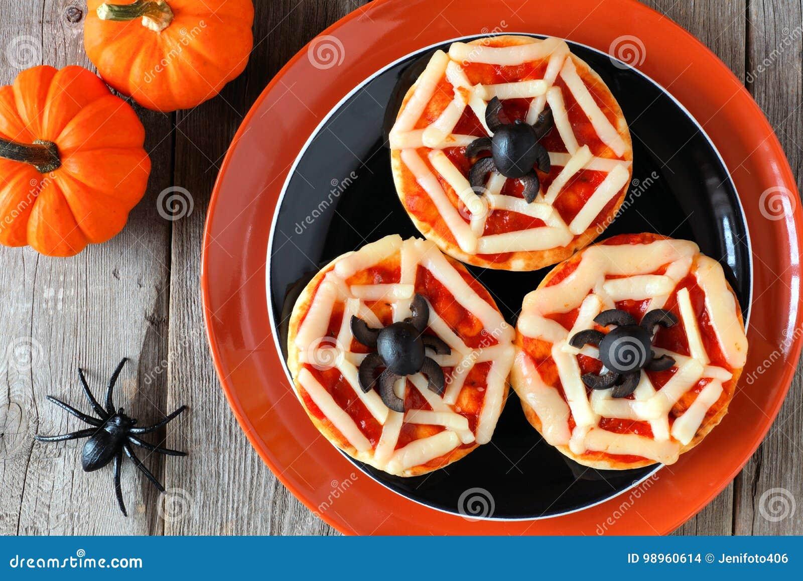 Pizzas del web de araña de Halloween mini en la placa negra y anaranjada