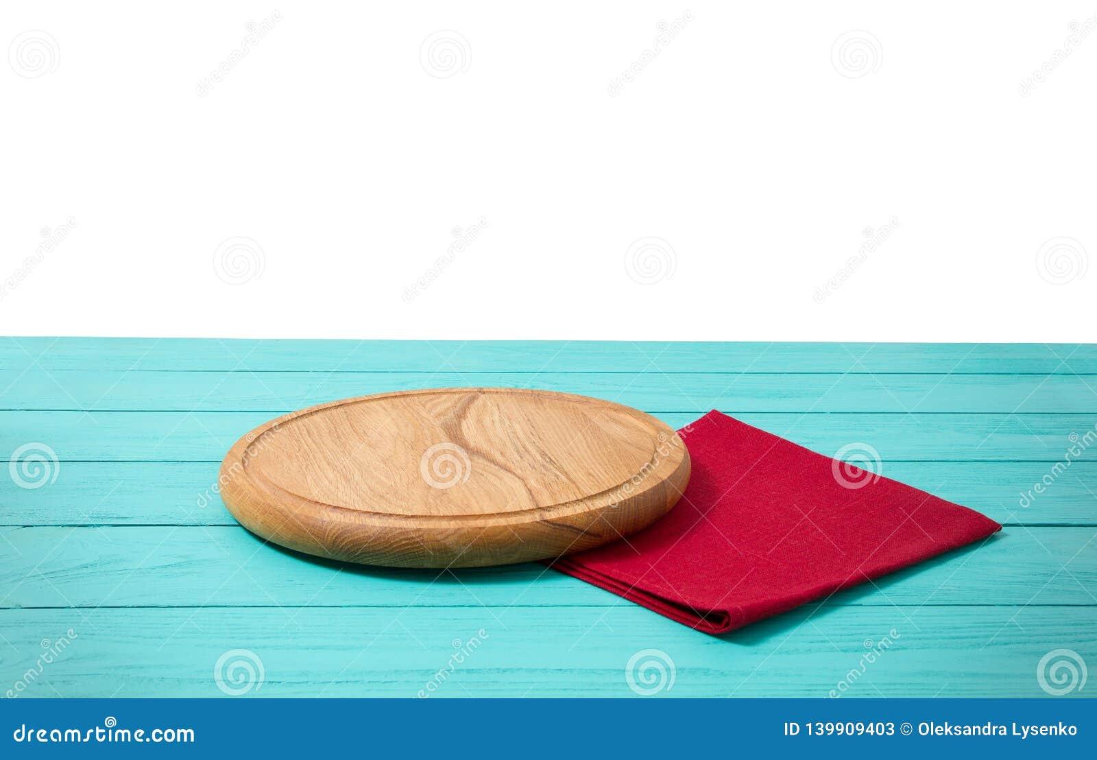 Pizzaskärbräda för runt trä och röd bordduk på den blåa trätabellen som isoleras på vit bakgrund Utrymme för bästa sikt och kopie