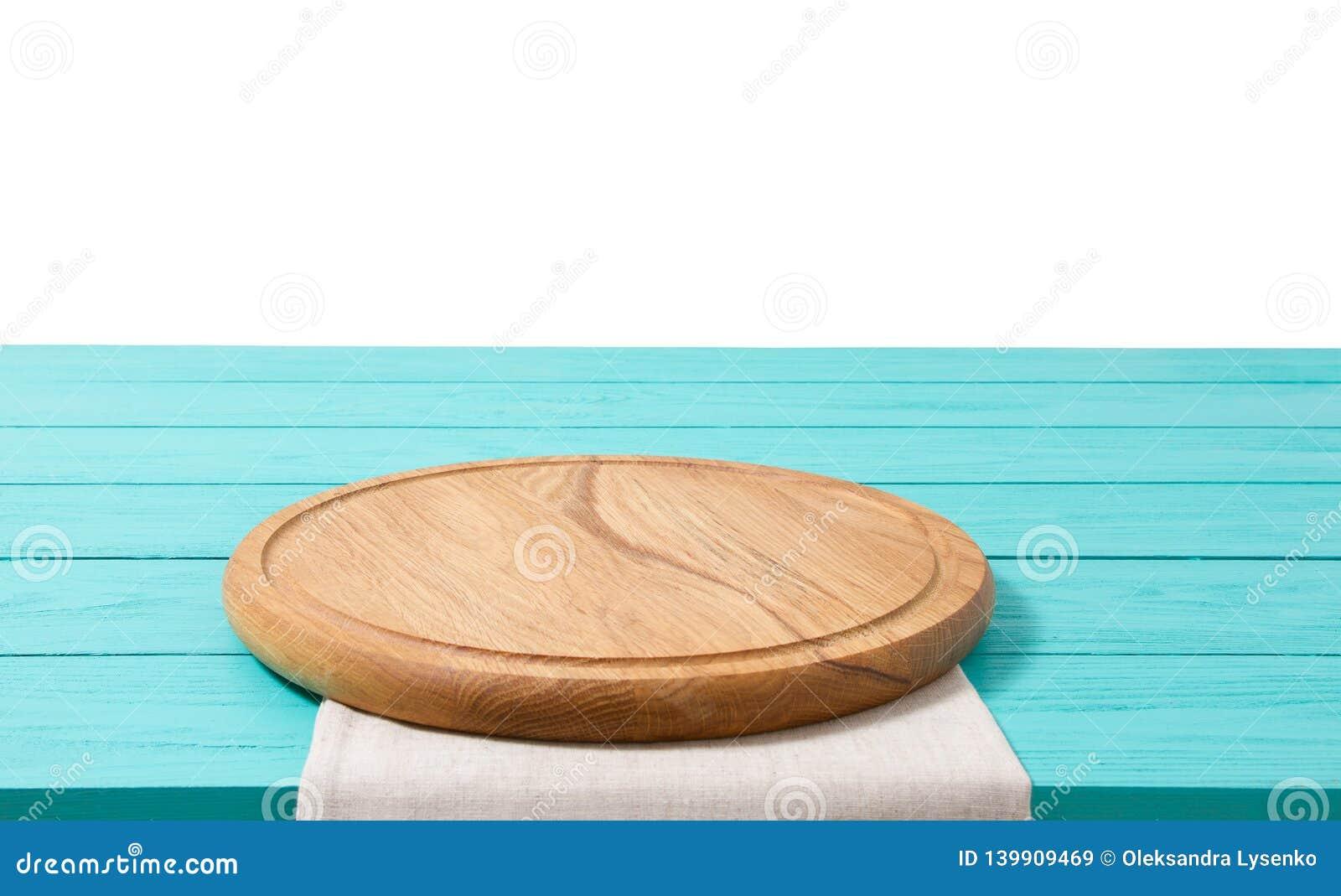 Pizzaskärbräda och bordduk för runt trä på den blåa trätabellen som isoleras på vit bakgrund Utrymme för bästa sikt som och kopie