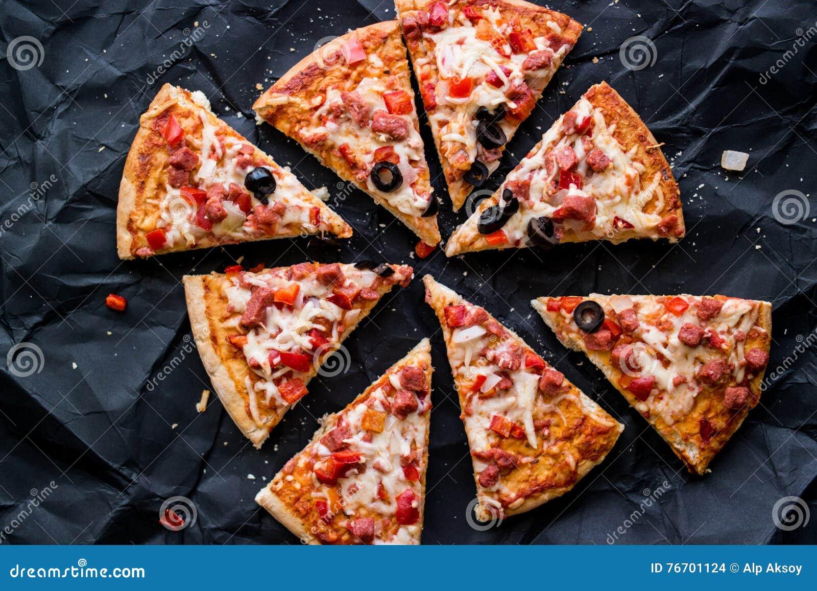 Pizzaskivor med skinka, ost och oliv på en svart yttersida