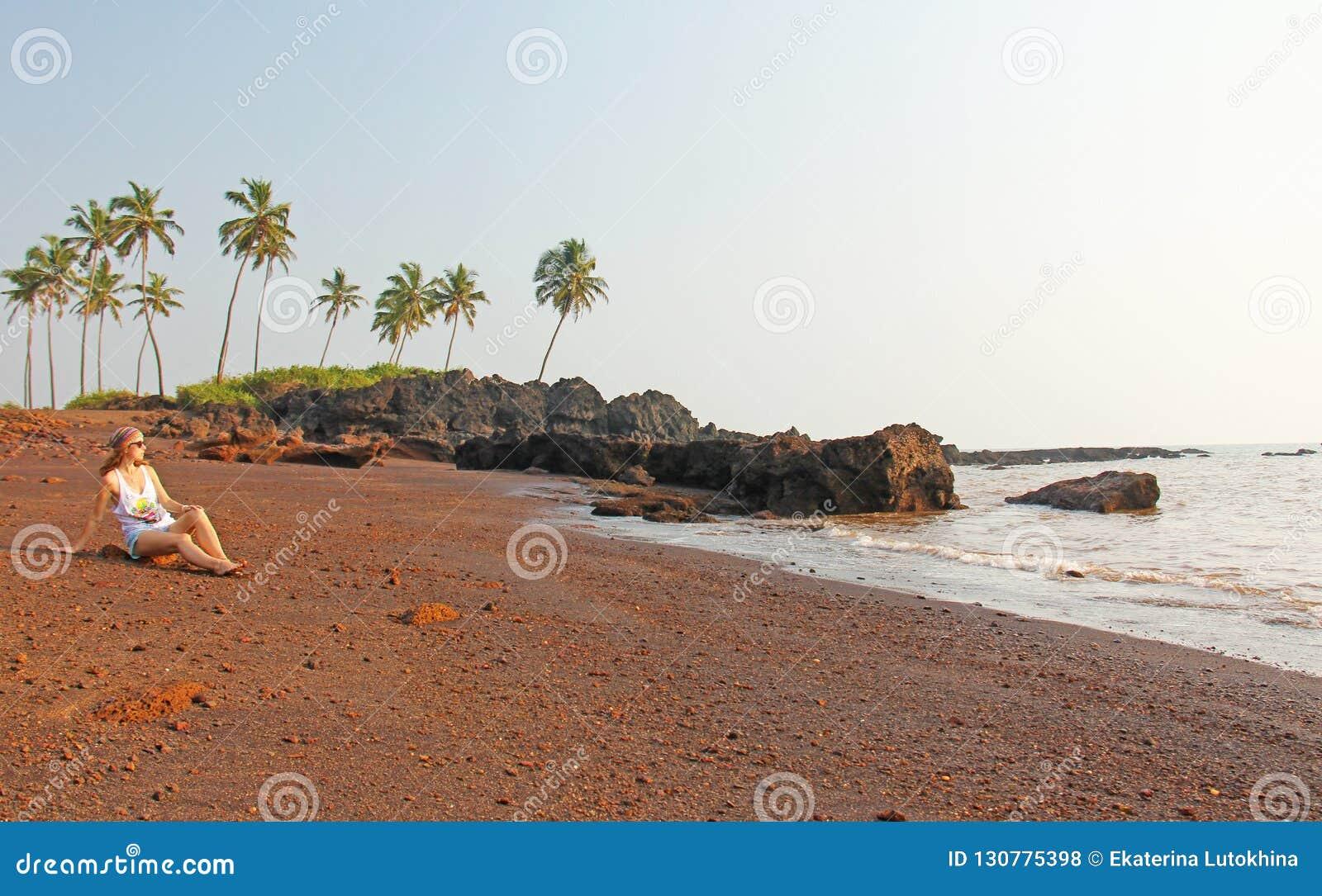 Plaża z czarnymi drzewkami palmowymi i piaskiem Ciemnego brązu powulkaniczny piasek a