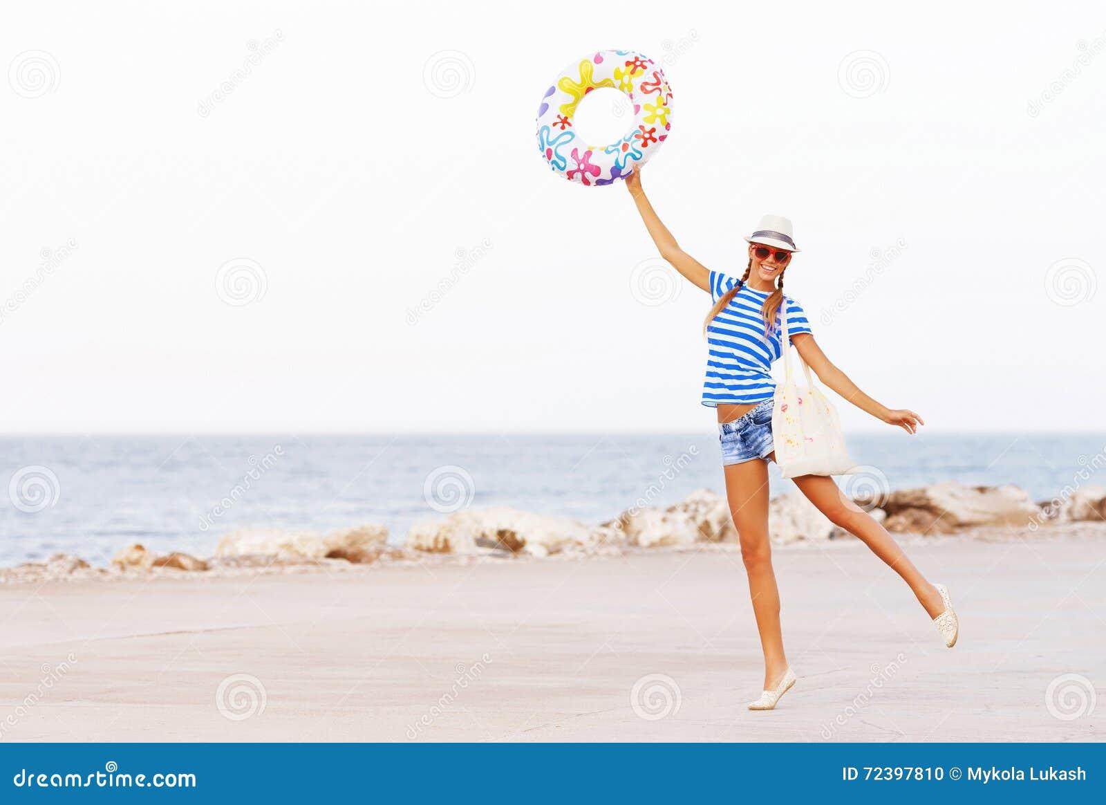 Plażowa kobieta szczęśliwa, kolorowi jest ubranym okulary przeciwsłoneczni i plażowy kapelusz ma lato zabawę podczas podróż wakac
