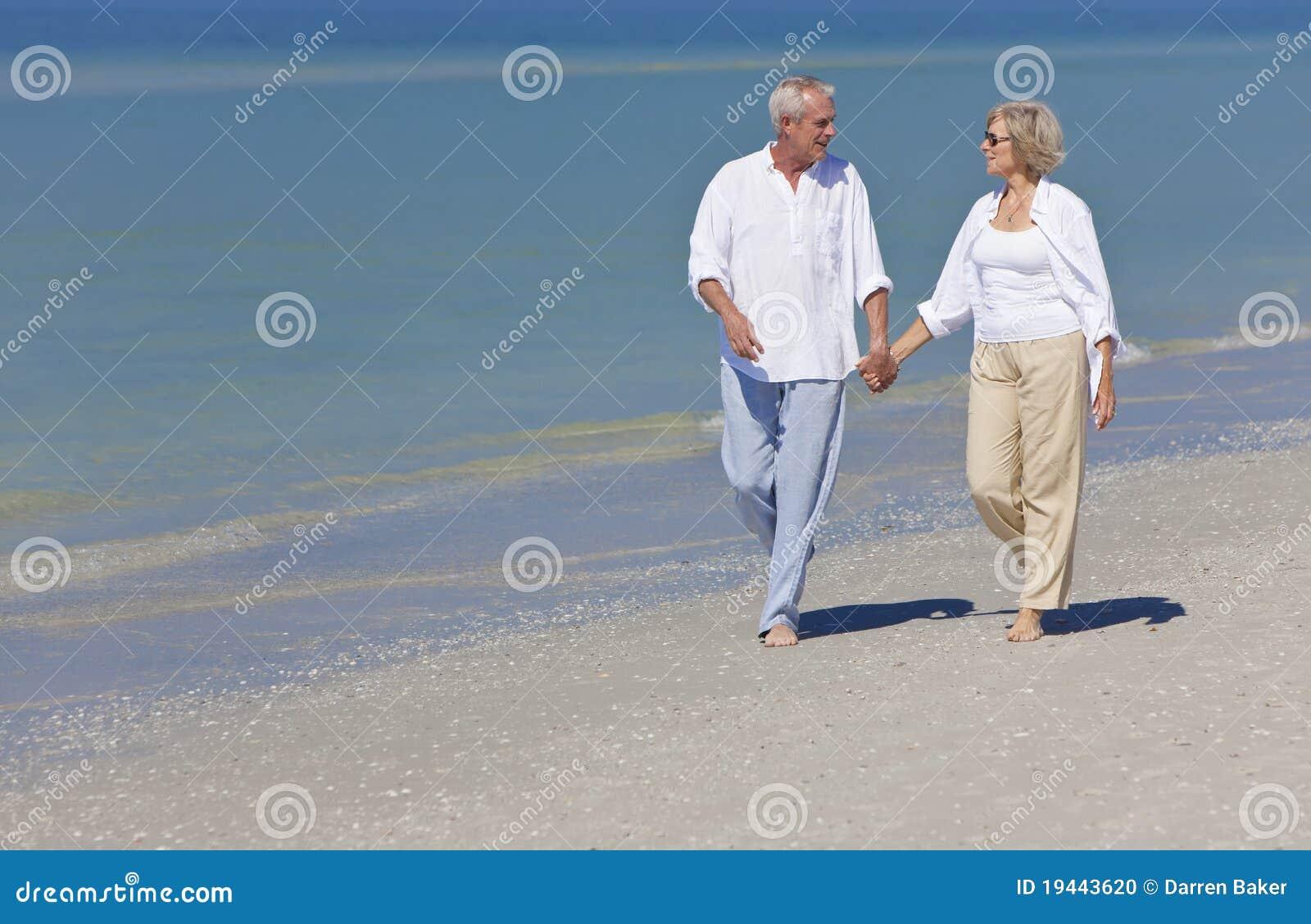 Plażowa para wręcza szczęśliwego mienia seniora odprowadzenie