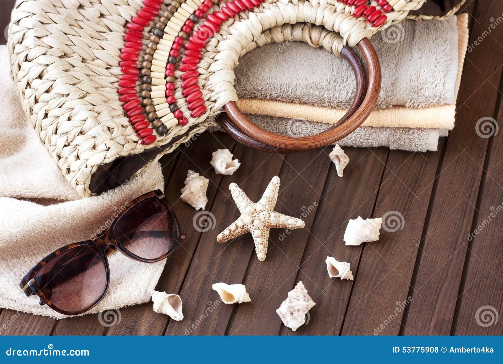 Plażowa torba i okulary przeciwsłoneczni na drewnianym tle