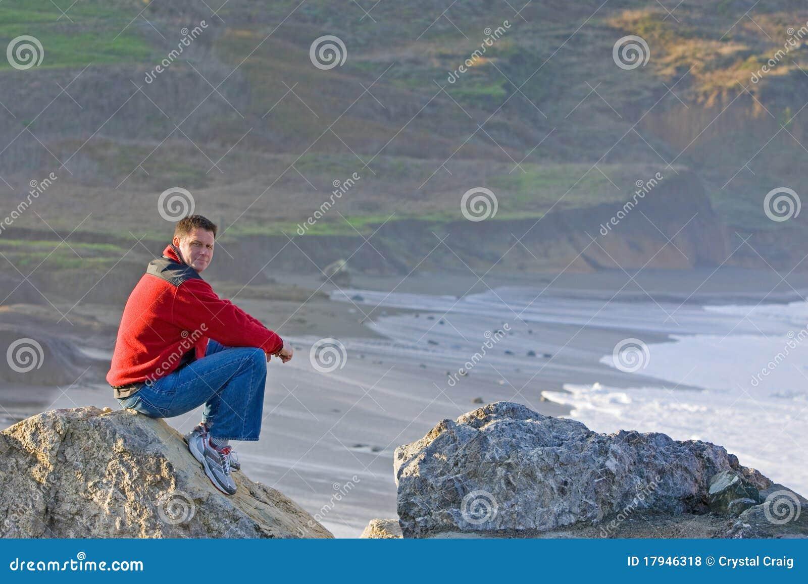Plażowego mężczyzna skalisty obsiadanie