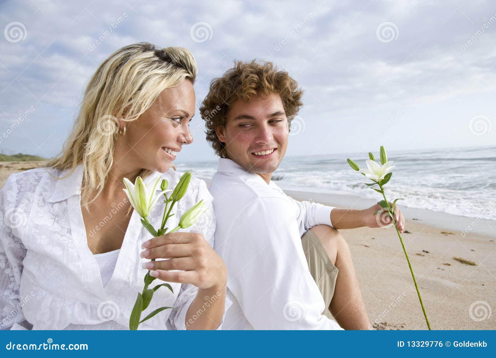 Plażowej pary szczęśliwi ciężarni relaksujący potomstwa
