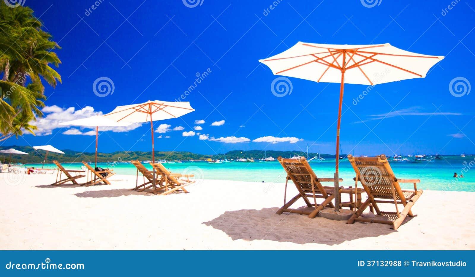 Plażowi krzesła na egzotycznej tropikalnej białej piaskowatej plaży
