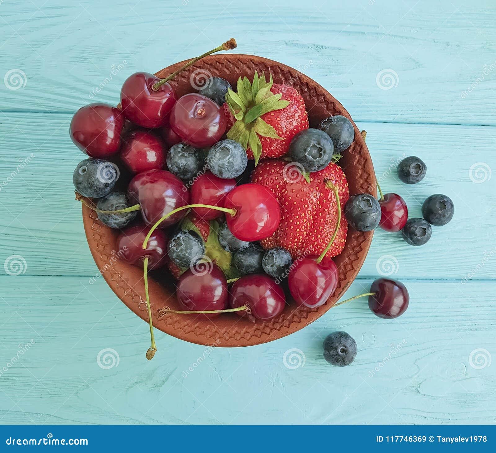 Plaat, fruitbessen, kers, aardbei, bosbessendessert op een blauwe houten achtergrond