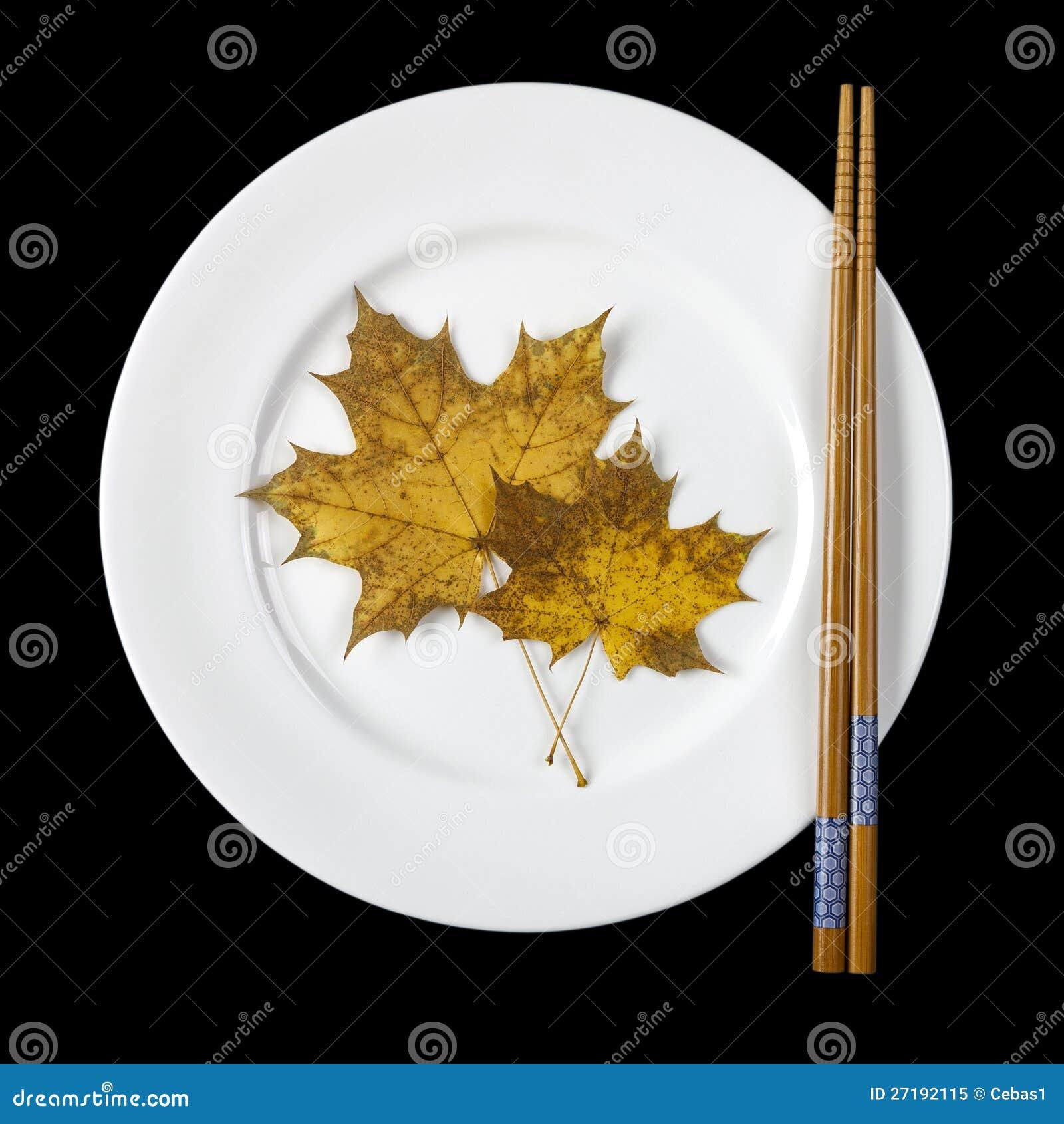 Plaat met eetstokjes en esdoornbladeren