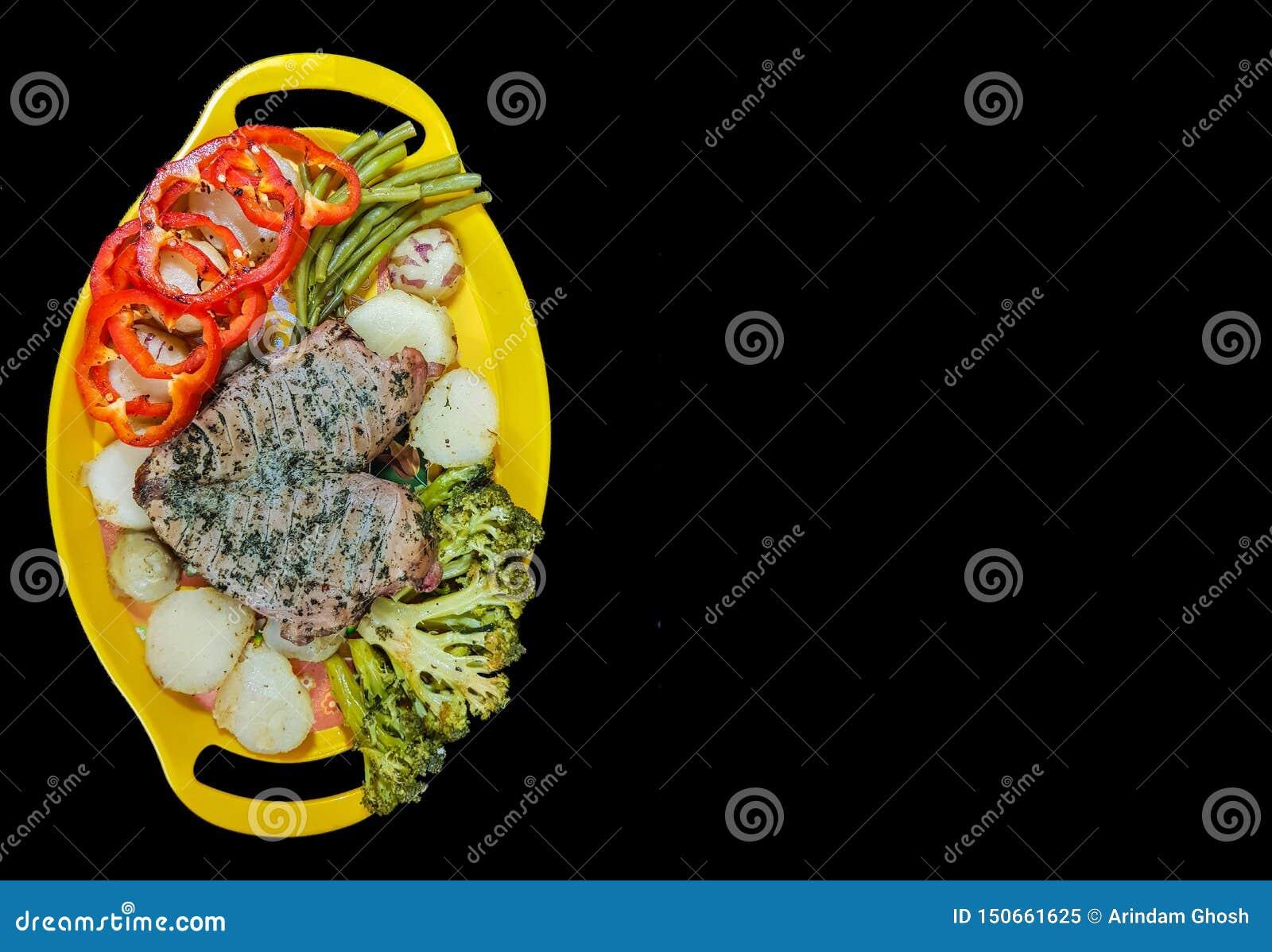 Plaat van lapje vlees en groenten op een gele plaat op een zwarte achtergrond met ruimte voor tekst