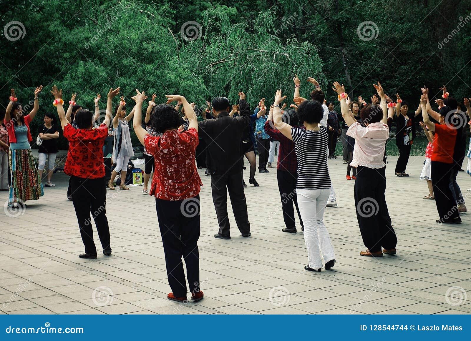 Plaatselijke bevolking die een danstai chioefening in een openbare parktuin hebben