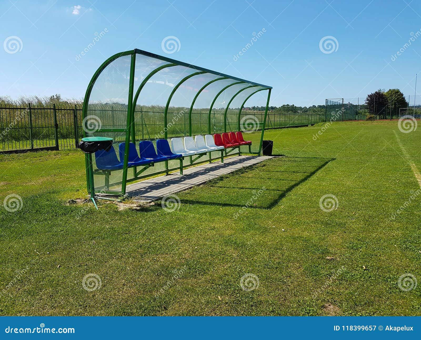 Plaatsen voor bussen en reservespelers op het voetbalgebied Plastiek gekleurde banken onder een luifel van transparante glasvezel