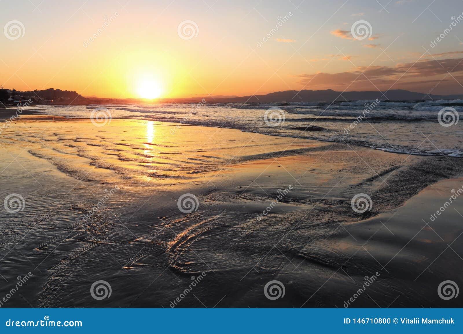 Plaatsplaats Agia Marina Beach, eiland Kreta, Griekenland De overzeese kust spangled door rotsen, de zonsopgang overdenkt het nat