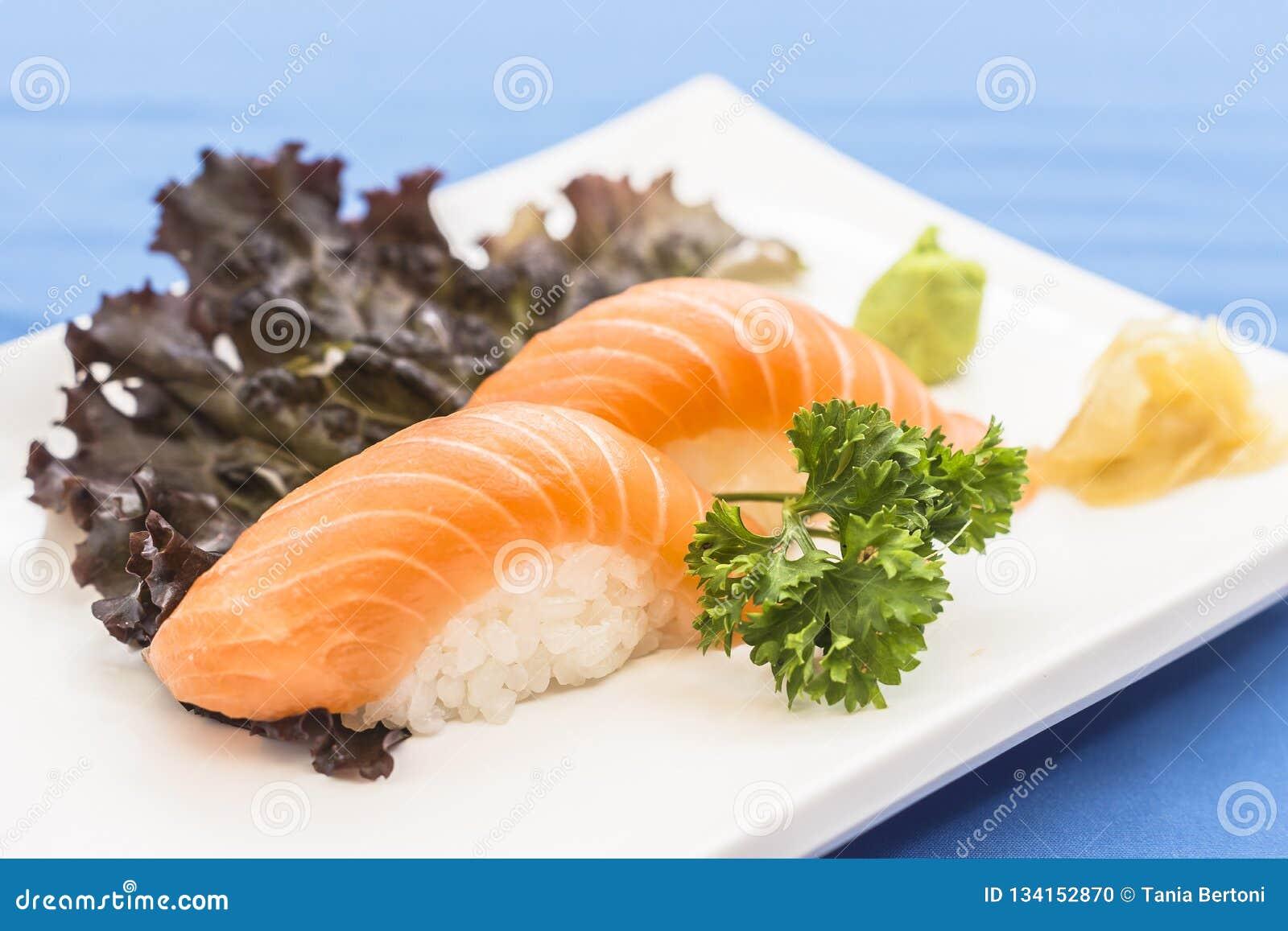Placa branca com o nigiri dos salmões com gengibre e wasabi